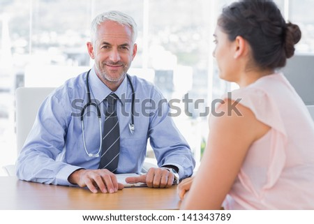 Attractive doctor sitting in front of patient in the office at desk - stock photo