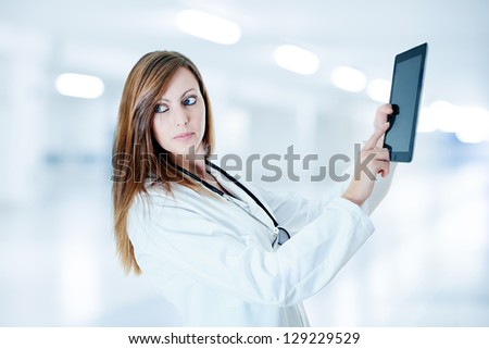 attractive doctor working with digital tablet at hospital - stock photo