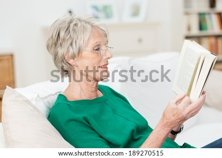 Attractive elderly woman reading a book at home smiling quietly to herself as she relaxes on a comfortable couch