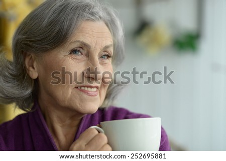 Attractive elderly woman with cup of coffee - stock photo