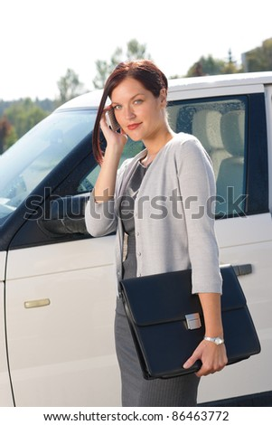 Attractive elegant business woman near luxury car hold briefcase calling - stock photo