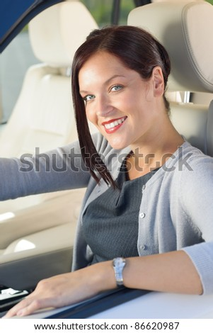 Attractive elegant businesswoman driving luxury car smiling at camera