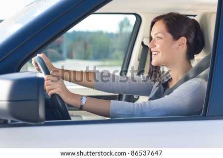 Attractive elegant businesswoman driving luxury new car concentrating - stock photo