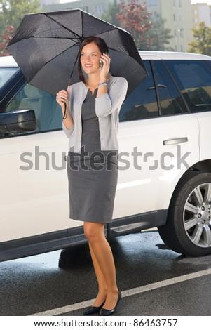 Attractive elegant businesswoman under umbrella by luxury car calling phone - stock photo