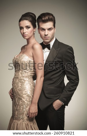 Attractive elegant man holding his lover while looking at the camera. - stock photo