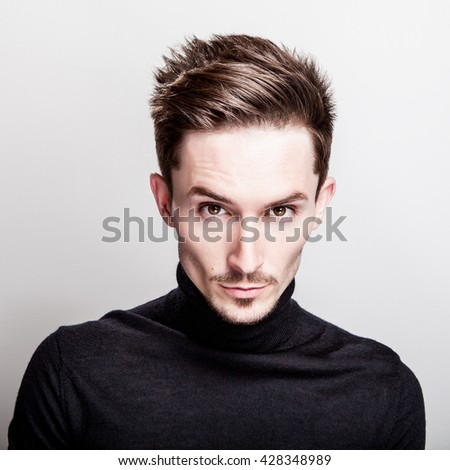 Attractive elegant man in black golf posing on light gray background.