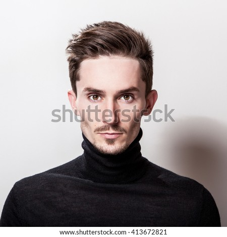 Attractive elegant man in black sweater posing on light gray background.