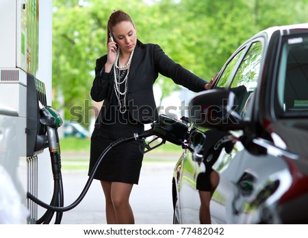 attractive elegant woman in black dress refuel car and talking to mobile phone - stock photo