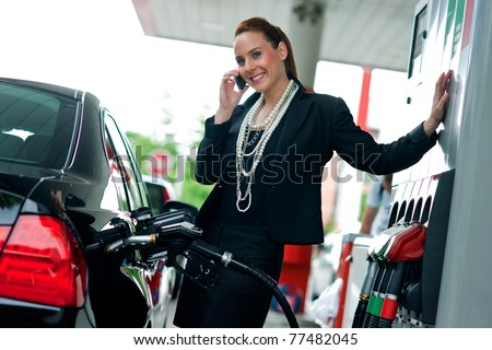 attractive elegant woman in black dress refuel car and talking to mobile phone