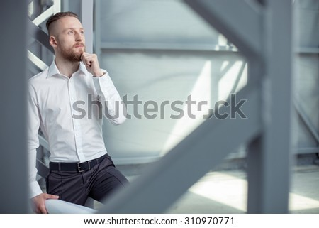Attractive engineer is dreaming about new project. He is looking up pensively and touching his chin. The man is holding a blueprint. Copy space in right side - stock photo