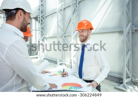 Attractive engineers are planning the new building. They are working with sketches and standing near the table. The men are smiling and looking at each other with trust - stock photo