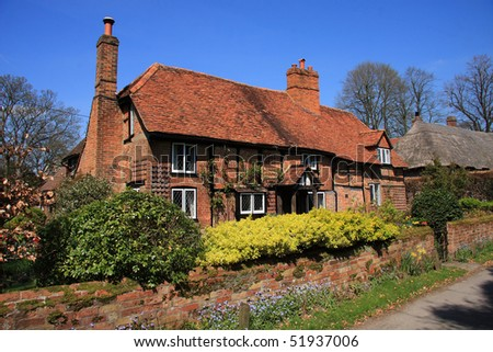 Attractive English medieval brick and timber cottage with garden wall and shrubs - stock photo