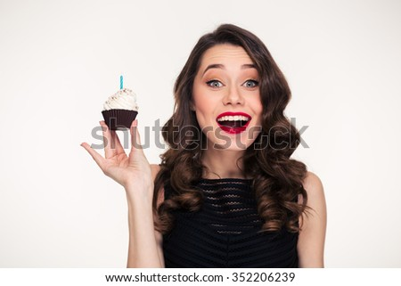Attractive excited smiling young woman with bright makeup in retro style holding birthday cupcake with candle  - stock photo