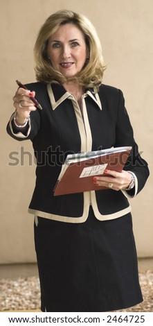 attractive executive business woman extends a pen - stock photo