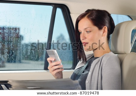 Attractive executive businesswoman sitting in car looking phone holding newspapers