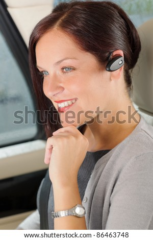 Attractive executive female manager sitting in car backseat calling hands-free