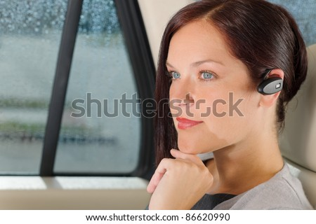 Attractive executive female manager sitting in car backseat calling hands-free - stock photo