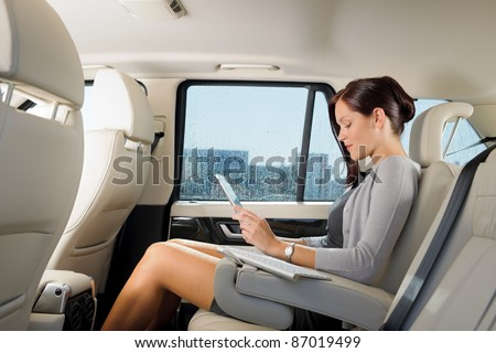 Attractive executive female manager work luxury car touch tablet computer - stock photo