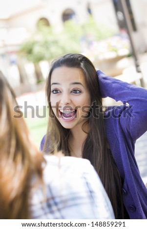Attractive Expressive Young Mixed Race Female Student Sitting and Talking with Girlfriend Outside on Bench. - stock photo