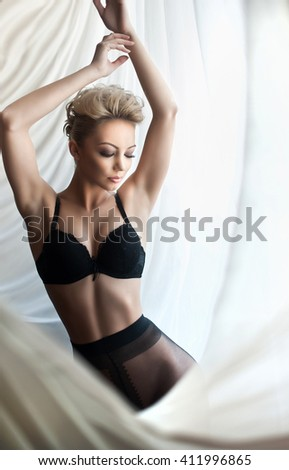 Attractive fair hair model with black pantyhose and bra posing provocatively wrapped in white curtains. Portrait of sensual short hair blonde in daylight. Beautiful female in window posing alone. - stock photo