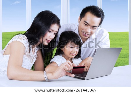 Attractive family doing online shopping by using laptop computer and credit card at home - stock photo