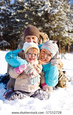 Attractive family having fun in a winter park - stock photo