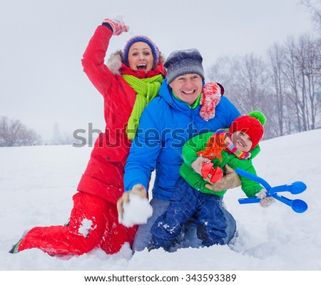 Attractive family of three having fun in a snow winter park - stock photo