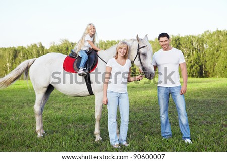Attractive family with a horse - stock photo