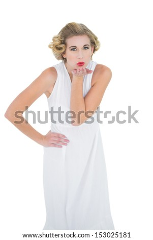 Attractive fashion blonde model blowing a kiss to the camera on white background - stock photo