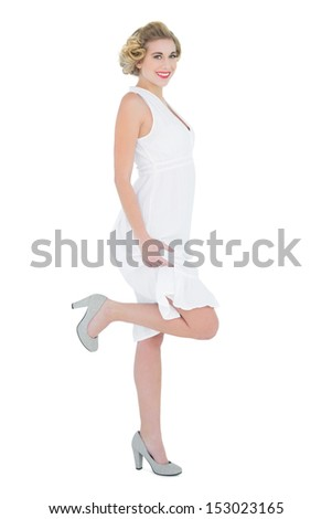 Attractive fashion blonde model posing with a leg up on white background - stock photo
