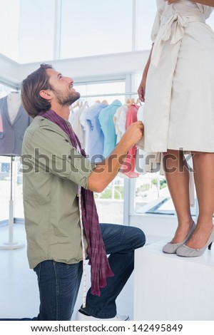 Attractive fashion designer looking at model