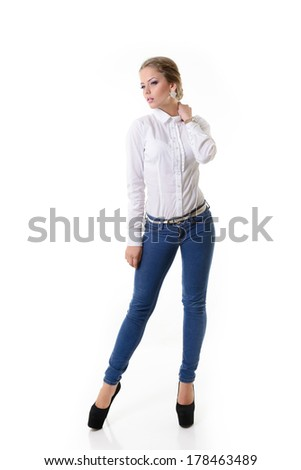 Attractive fashion girl in blue jeans and white shirt, full length portrait over white - stock photo