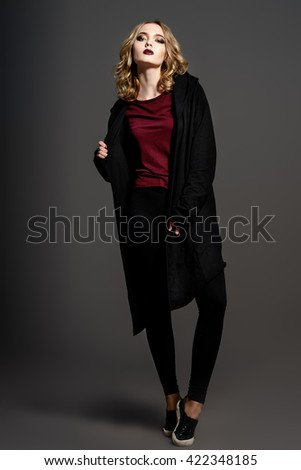 Attractive fashion girl with dark make-up posing in black clothes. Beauty, fashion. Cosmetics. - stock photo