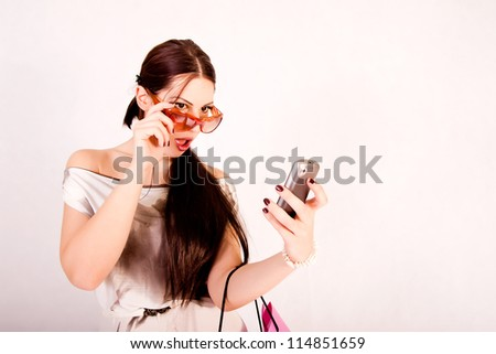 Attractive fashion model looking at her cell phone - stock photo