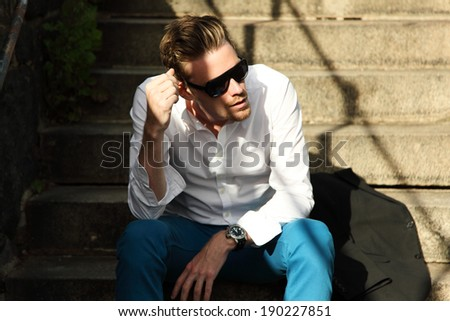 Attractive fashion model sitting down outside wearing a white shirt and black sunglasses.  - stock photo
