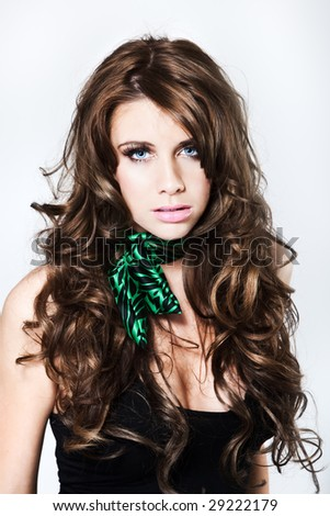 Attractive fashion model with curly hair looking into camera - stock photo
