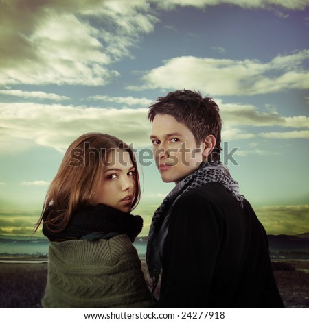 attractive fashion models as couple in love holding in nature against dramatic sky - stock photo