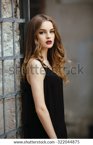 Attractive fashion woman in black dress  posing near white wall - stock photo