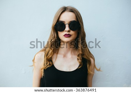 Attractive fashion woman in black dress with sunglasses posing near white wall - stock photo