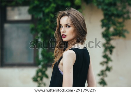 Attractive fashion woman in orange dress  posing near white house - stock photo