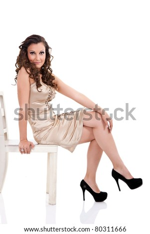 attractive fashion woman sitting on retro chair, isolated on white background - stock photo