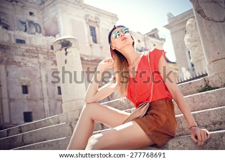 Attractive fashionable blonde woman relaxing, sitting. Girl wearing sunglasses. Sunny vacation day. - stock photo