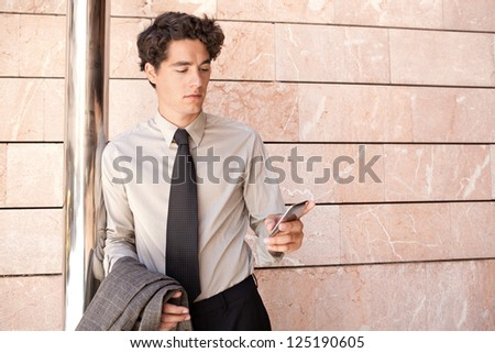 Attractive fashionable businessman wearing an elegant suit and shades, leaning on a modern office building in the city and using a smart phone. - stock photo