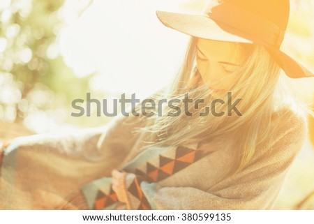 Attractive fashionable girl in a hat and poncho walking at sunny day outdoor - stock photo