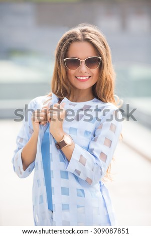 Attractive fashionable middle-aged woman standing in a street looking thoughtfully at the camera with a charming friendly smile. - stock photo