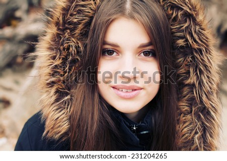 Attractive fashionable stylish young woman in wintertime outdoor. Portrait of happy young pretty funny smiling girl in cold weather dressed in warm clothes.  - stock photo