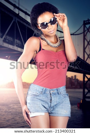 Attractive fashionable young african woman posing outdoor, wearing sunglasses. - stock photo