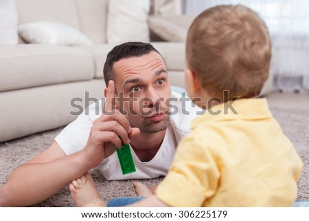 Attractive father is lying on flooring near his small son. He is raising his finger up and explaining something to his child with seriousness. The boy is listening to him attentively - stock photo