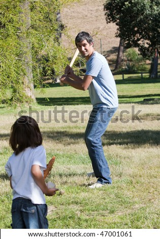 Attractive father playing baseball with his son in the park - stock photo