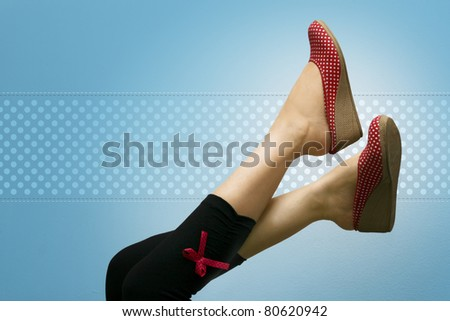 Attractive feet high up, showing red polka dotted shoes, against a vignette blue background with polka dots. - stock photo